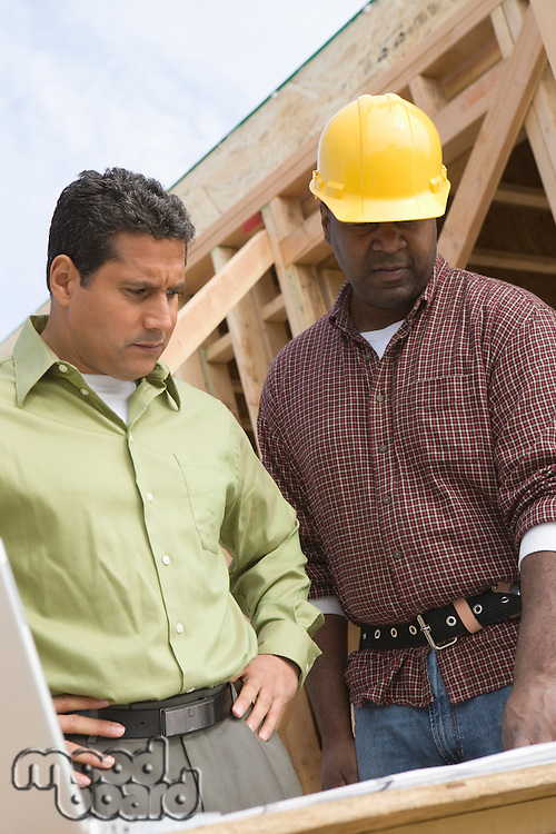 Architect and construction worker examining structure on construction site