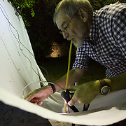 An entomologist uses an aspirator to collect tiny beetles off a sheet while blacklighting for insects