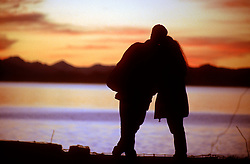 """Bariloche, Argentina. Abril/2004.Casal em olha para o por-do-sol no Lago Nahuel Huapi. Bariloche e uma cidade da Argentina localizada na Provincia de Rio Negro, junto a Cordilheira dos Andes na fronteira com o Chile. A principal atividade economica de Bariloche e o turismo. Alem das montanhas onde se podem praticar esqui e """"snowboard""""./ Couple watching sunset. Bariloche is a city in the province of Rio Negro, Argentina, situated on the foothills of the Andes, surrounded by lakes and mountains. It is famous for skiing but also great for sight-seeing, water sports, trekking and climbing. Cerro Catedral is one of the most important ski centers in South America..Foto Marcos Issa/Argosfoto"""