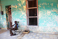 Man on rocking chair on a porch in San Antonio de Rio Blanco, Mayabeque, Cuba.