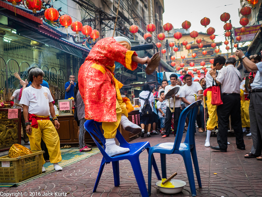 "08 FEBRUARY 2016 - BANGKOK, THAILAND:  A member of a lion dance troupe stands on a chair that's about to collapse during his performance for Chinese New Year at a small Chinese shrine in Bangkok's Chinatown district, during the celebration of the Lunar New Year. Chinese New Year is also called Lunar New Year or Tet (in Vietnamese communities). This year is the ""Year of the Monkey."" Thailand has the largest overseas Chinese population in the world; about 14 percent of Thais are of Chinese ancestry and some Chinese holidays, especially Chinese New Year, are widely celebrated in Thailand.      PHOTO BY JACK KURTZ"