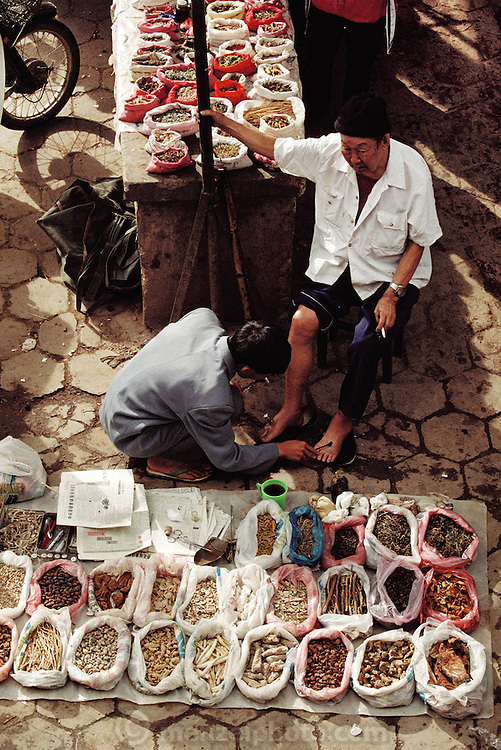 "Menghan Sunday market. A ""Barefoot"" Doctor using herbal healing in Xishaungbanna, China."