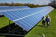 Two British men walk along a large solar power energy panel in a field in Wadebridge, Cornwall, UK.