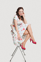 Portrait of beautiful young woman in dress sitting on stool against white background