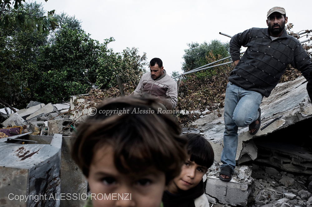 "Gaza Strip: Members of the Palestinian al-Attar family, displaced during the eight-day conflict with Israel, return to their home in the al-Atatra area in the northern Gaza Strip. Their house was bombed four years before too, during ""Cast lead"" Israeli Defense Force operation. ALESSIO ROMENZI"