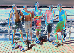 Group of young men standing together on seafront laughing,