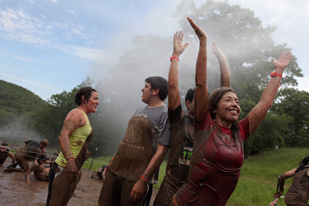 "Competitors enjoy the water sprayed out of a snow-maker used to muddy the barbed-wire crawl hill after finishing the obstacle during the Spartan Sprint at the Tuxedo Ridge Ski Center in Orange County on June 4, 2011. Competitors faced several obstacles, including the muddy 40-yard uphill barbed-wire crawl, an ice pit, fire pit and the final run through a gauntlet of muscled ""gladiators."" ( Xavier Mascareñas / The Journal News )"