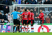 Southampton players surround referee David Coote to protest a potential hand ball during the Premier League match between Newcastle United and Southampton at St. James's Park, Newcastle, England on 8 December 2019.