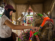 31 AUGUST 2014 - SARIKA, NAKHON NAYOK, THAILAND: A woman pours holy oil on a statue of Ganesh at Shri Utthayan Ganesha Temple in Sarika, Nakhon Nayok. Ganesh Chaturthi, also known as Vinayaka Chaturthi, is a Hindu festival dedicated to Lord Ganesh. It is a 10-day festival marking the birthday of Ganesh, who is widely worshiped for his auspicious beginnings. Ganesh is the patron of arts and sciences, the deity of intellect and wisdom -- identified by his elephant head. The holiday is celebrated for 10 days, in 2014, most Hindu temples will submerge their Ganesh shrines and deities on September 7. Wat Utthaya Ganesh in Nakhon Nayok province, is a Buddhist temple that venerates Ganesh, who is popular with Thai Buddhists. The temple draws both Buddhists and Hindus and celebrates the Ganesh holiday a week ahead of most other places.    PHOTO BY JACK KURTZ