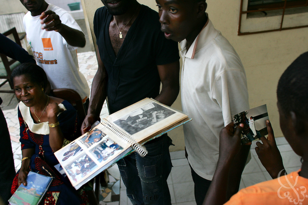 """The family of Ivory Coast national team member Didier """"Maestro"""" Zokora look through a scrapbook of his news clippings and photos at their home in the Yopoungon neighborhood of Abidjan, Ivory Coast February 18, 2006. Zokora's mother Alphonsine (l), has founded a group called the """"mothers of the football playing elephants"""" that meets monthly with the other mothers of national team members."""