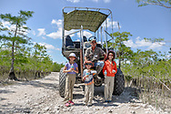 Kids stand with their guide at the back of a towering swamp buggy on a break in a dry zone of Big Cypress National Preserve.
