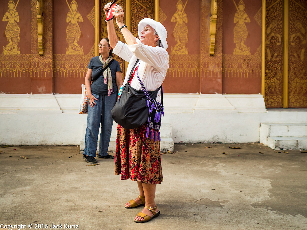 "12 MARCH 2016 - LUANG PRABANG, LAOS:  Tourists at Wat Sensoukharam in Luang Prabang. Luang Prabang was named a UNESCO World Heritage Site in 1995. The move saved the city's colonial architecture but the explosion of mass tourism has taken a toll on the city's soul. According to one recent study, a small plot of land that sold for $8,000 three years ago now goes for $120,000. Many longtime residents are selling their homes and moving to small developments around the city. The old homes are then converted to guesthouses, restaurants and spas. The city is famous for the morning ""tak bat,"" or monks' morning alms rounds. Every morning hundreds of Buddhist monks come out before dawn and walk in a silent procession through the city accepting alms from residents. Now, most of the people presenting alms to the monks are tourists, since so many Lao people have moved outside of the city center. About 50,000 people are thought to live in the Luang Prabang area, the city received more than 530,000 tourists in 2014.      PHOTO BY JACK KURTZ"
