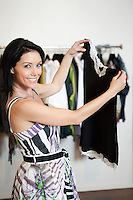 Portrait of a beautiful mid adult woman standing with top in fashion shop