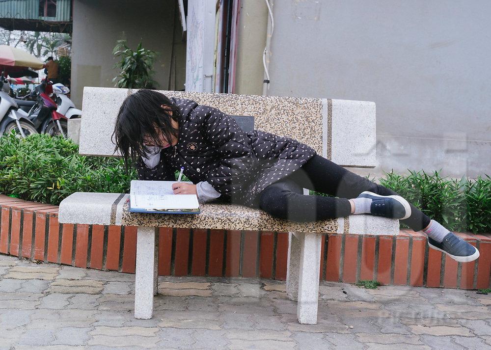 Young Vietnamese girl doing her homework on a bench, Hanoi, Vietnam, Southeast Asia