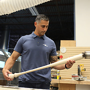 Pete Tucci, checks a baseball bat from the wood lathe in his factory, Tucci Lumber Company, which makes baseball bats. Norwalk, Connecticut, USA. 27th June 2014. Photo Tim Clayton