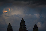 The sunsets beyond a storm cloud with the Angkor Wat towers in the foreground.