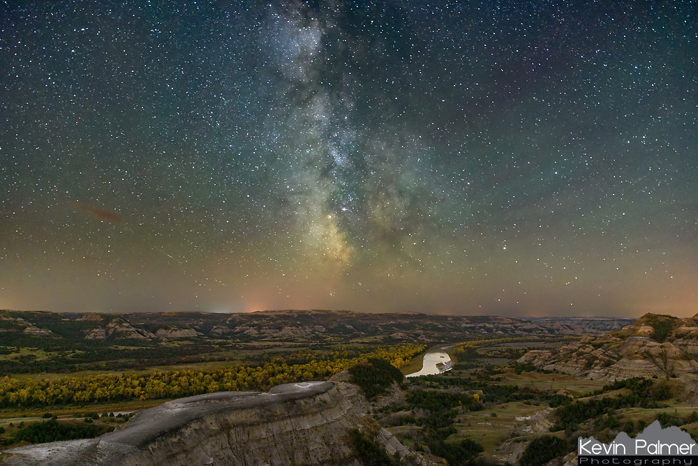 The milky way glows above the Little Missouri River, lined with golden cottonwood trees. Looking south, the skies were very dark here in the north unit of Theodore Roosevelt National Park. But there was a lot of light pollution present to the north from natural gas flaring in the Bakken oil field. This was taken on the last day of September.