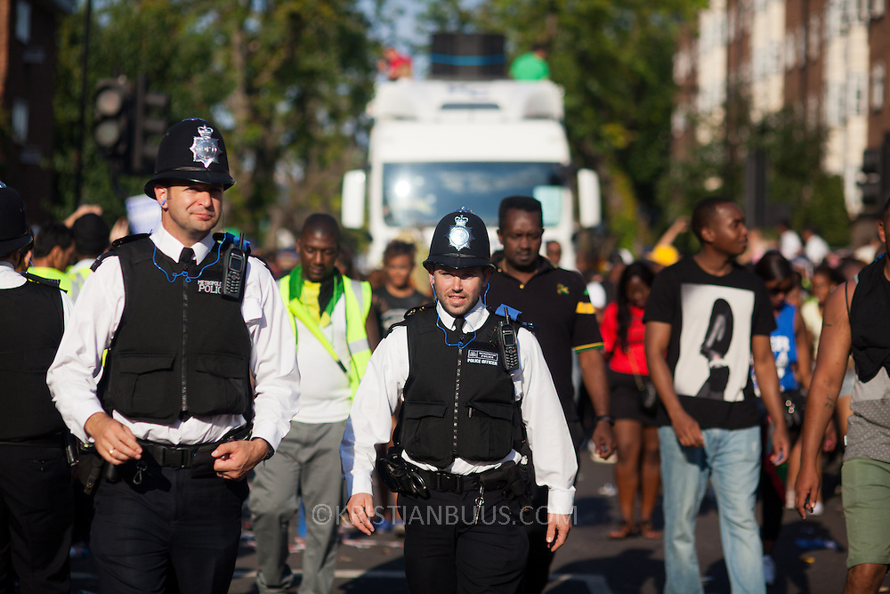 Police officers walk between passing trucks on the carnival route.The Notting Hill Carnival has been running since 1966 and is every year attended by up to a million people. The carnival is a mix of amazing dance parades and street parties with a distinct Caribbean feel.