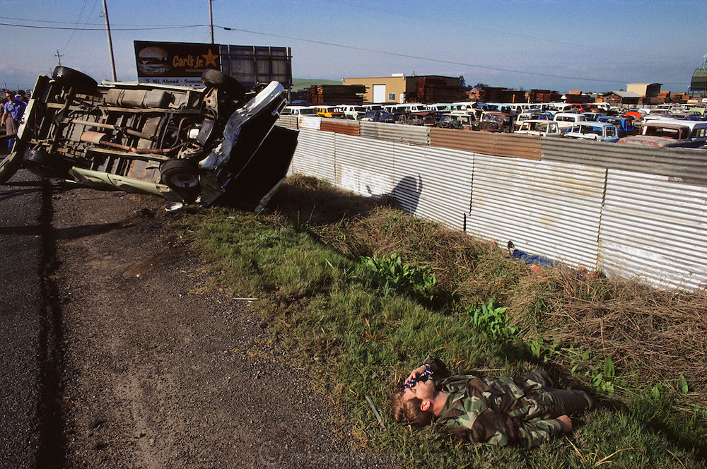 An overturned truck from an automobile accident, and a victim on the roadside of Highway 29, American Canyon, California. The accident took place in front of an auto wrecking yard. USA.