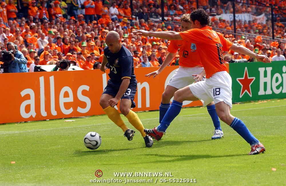 NLD/Rotterdam/20060604 - Vriendschappelijke wedstrijd Nederland - Australie, Jan Kromkamp (12) en Mark van Bommel (18) in duel met Marco Bresciano (23)