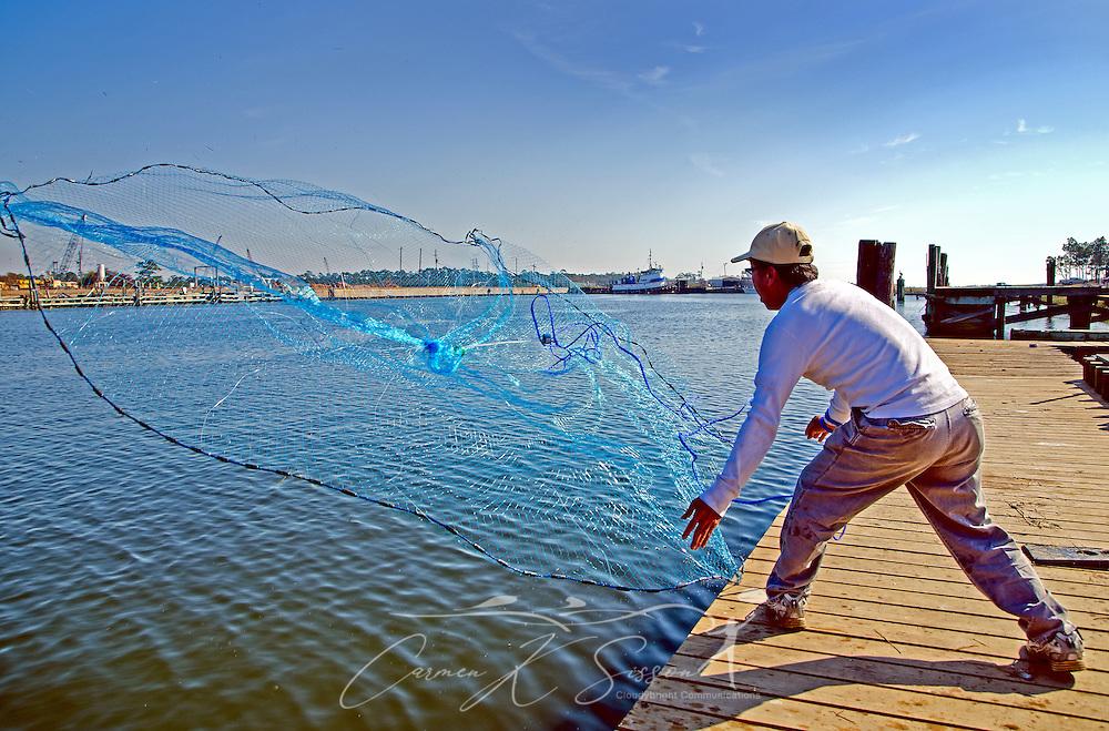 A man throws a cast net for fish in Bayou La Batre, Alabama, Nov. 23, 2012. (Photo by Carmen K. Sisson/Cloudybright)
