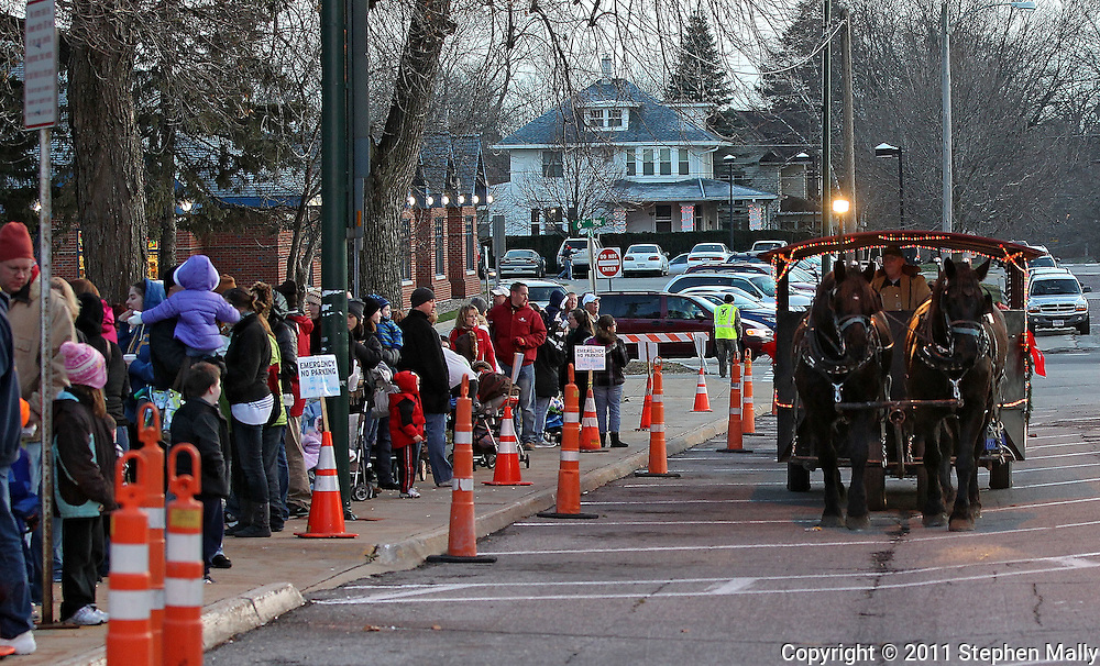 People waiting in line to see Santa and Mrs. Claus watch the horse-drawn carriage go by during Christmas in the Park and Peppermint Walk at City Square Park in Marion on Friday evening, December 2, 2011. (Stephen Mally/Freelance)
