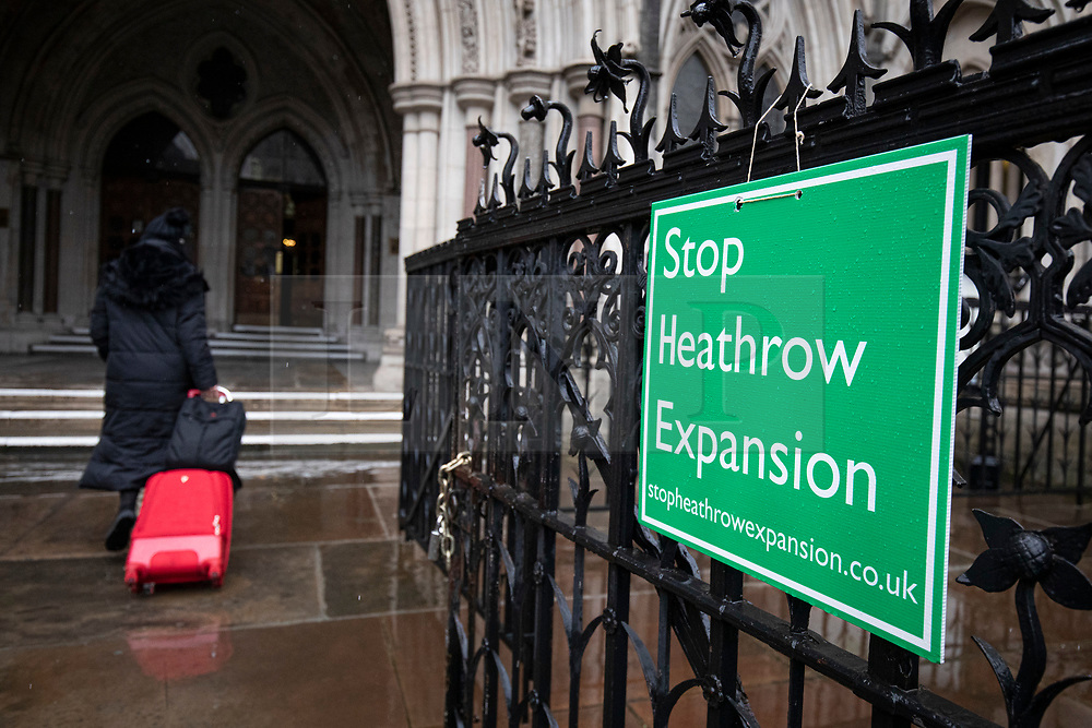 © Licensed to London News Pictures. 27/02/2020. London, UK. A woman walks in to the High Court as protesters who oppose the expansion of Heathrow Airport demonstrate outside. Judges will deliver their ruling on a number of appeals against the planned construction of a third runway at the London airport. Photo credit: Rob Pinney/LNP