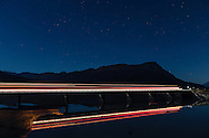 Truck lights reflected in Portage Creek along Turnagain Arm in Southcentral Alaska. Autumn. Evening.