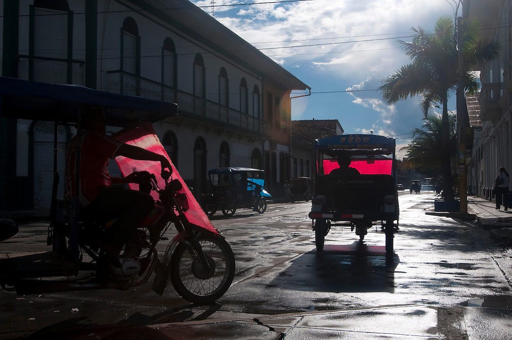 The city of Iquitos, Peru, is the largest in the world that has no roads leading to it.  As such, the streets are dominated by motorcycles and mototaxis that are shipped in by boat.  The weather changes in a moments notice in the Amazon and the mototaxi drivers have adapted by stringing up removable plastic sheets to shield them from the rain.