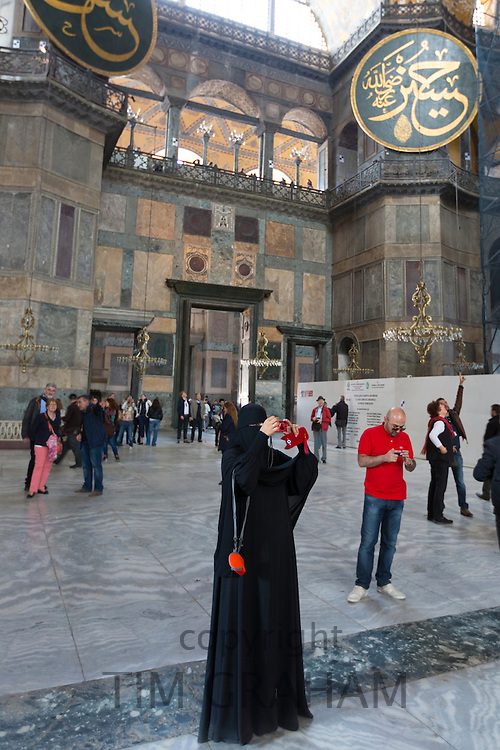 Muslim woman at Hagia Sophia, Ayasofya Muzesi mosque museum wearing niqab using smartphone taking photographs, Istanbul, Turkey