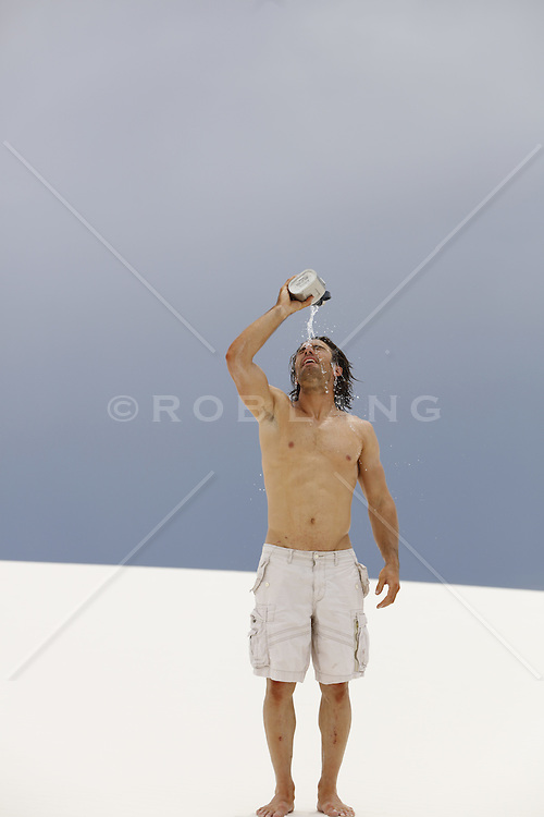 shirtless man in the desert pouring water over his head and body
