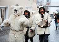 Imst Schemenlaufen, a traditional carnival held only once every four years in Imst, Tirol, Austria (31 January 2016). The Schemenlaufen is inscribed on the UNESCO list of Intangible Cultural Heritage. Pictured, one of the 'bear' characters withe his minders. © Rudolf Abraham