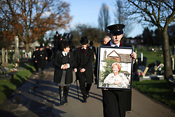 © Licensed to London News Pictures. 09/12/2015. London, UK. A man carrying a picture of Cynthia Payne as he leads the funeral procession.  The funeral of former brothel keeper Cynthia Payne takes place at the South London Crematorium.  In 1980 Cynthia Payne was sentenced to 18 months for running a brothel at her house on Ambleside Avenue in Streatham. It was alleged, at the time, that judges and Members of Parliament were visitors to her establishment. Photo credit: Peter Macdiarmid/LNP