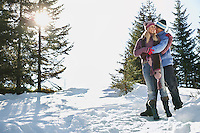 Couple standing on snow-covered hill