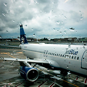 October 1, 2010 - Queens, NY : A jetBlue airplane sits at its gate at John F. Kennedy airport on a rainy day in October. Droplets of rain punctuate the foreground.