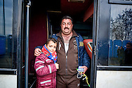 Saad Tawa (C) 41 years old, a Christian of Mosul Iraq,with his son, arrived with his family in Greece after a journey of 14 months  to arrive in Amsterdan  where he will reunite with the rest of the family, 8 Febraury 2016. Hundreds of refugees  wait every day at a gas station used as a temporary camp outside of Polykastro city at the north part of Greece until they receive the order from the police to move to the Greece- Macedonian border and continue their trip  to North Europe.