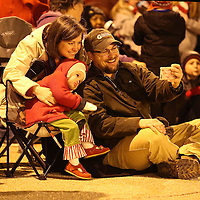 Adam Robison | BUY AT PHOTOS.DJOURNAL.COM<br /> Gregg Garner takes a picture with his wife Rachel and there daughter Samantha, 2, as the wait on Main Street for the Tupelo Christmas Parade to start Friday night.