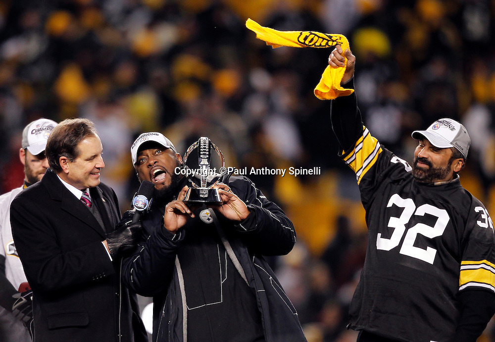 Pittsburgh Steelers head coach Mike Tomlin talks to sportscaster Jim Nantz  (left) as he holds up the AFC Champion Lamar Hunt Trophy during the postgame trophy presentation after winning the NFL 2011 AFC Championship playoff football game against the New York Jets on Sunday, January 23, 2011 in Pittsburgh, Pennsylvania. Waving a terrible towel is former Steelers running back Franco Harris (right). The Steelers won the game 24-19. (©Paul Anthony Spinelli)