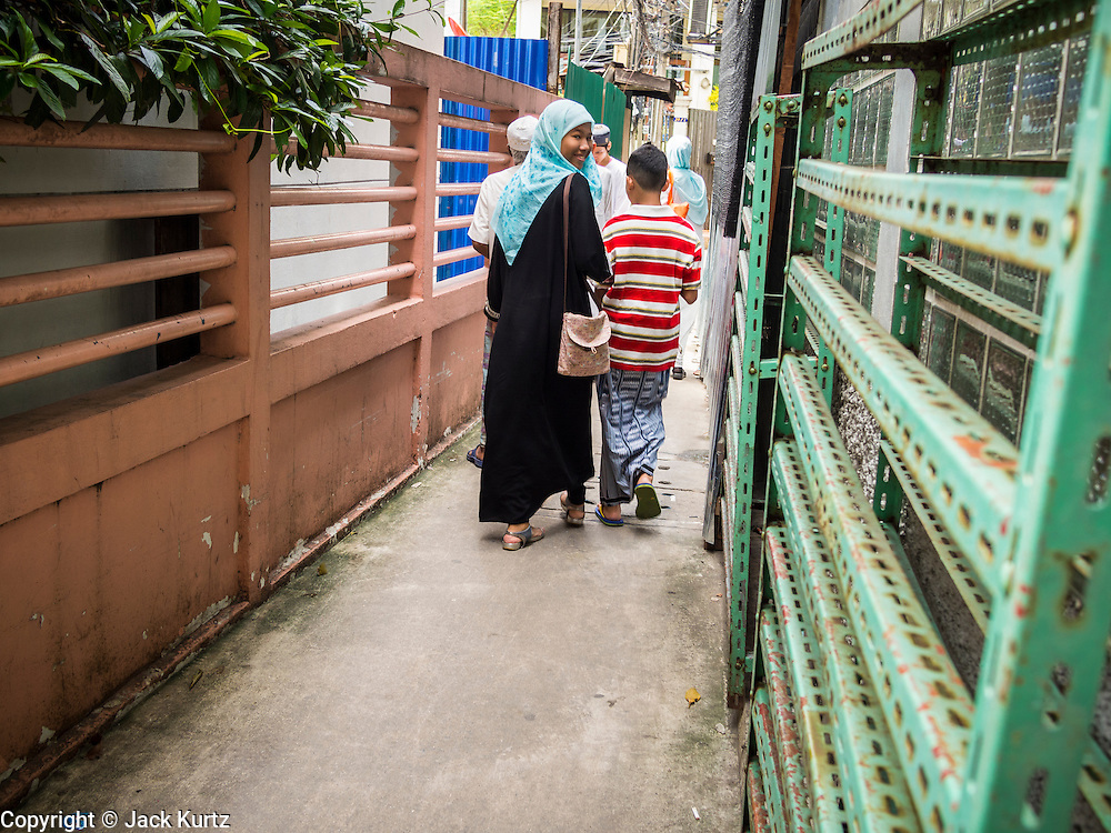 "08 AUGUST 2013 - BANGKOK, THAILAND: A family walks down an alley next to Haroon Mosque in Bangkok after Eid al-Fitr services. Eid al-Fitr is the ""festival of breaking of the fast,"" it's also called the Lesser Eid. It's an important religious holiday celebrated by Muslims worldwide that marks the end of Ramadan, the Islamic holy month of fasting. The religious Eid is a single day and Muslims are not permitted to fast that day. The holiday celebrates the conclusion of the 29 or 30 days of dawn-to-sunset fasting during the entire month of Ramadan. This is a day when Muslims around the world show a common goal of unity. The date for the start of any lunar Hijri month varies based on the observation of new moon by local religious authorities, so the exact day of celebration varies by locality.      PHOTO BY JACK KURTZ"