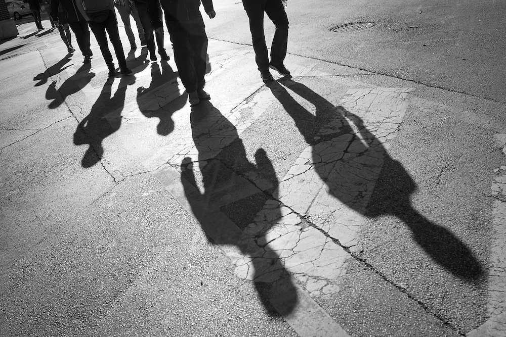 Street photograph of shadows march across the street in Chicago, Illinois.