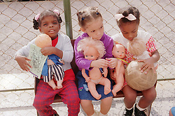 Nursery school children with dolls sitting on a bench in school playground in Havana; Cuba,