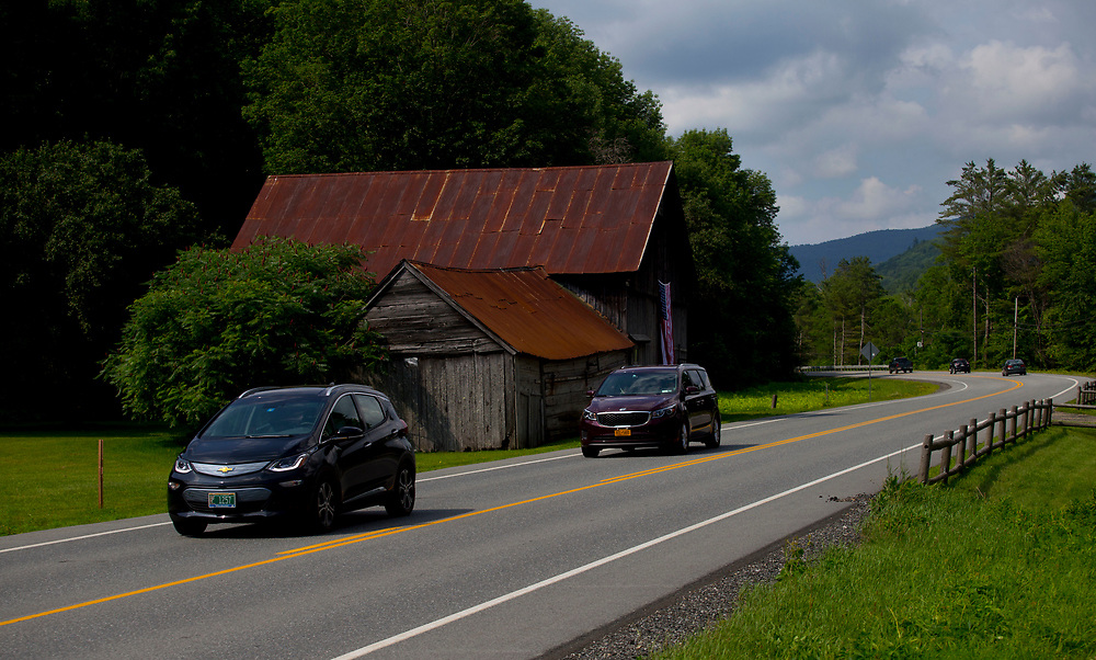 Kevin Jones, of Chittenden, Vt., travels on Route 107 in Bethel, Vt., to his job on July 12, 2017. After owning two gas-electric hybrids, Jones decided to lease a Chevy Bolt electric car for his 80-mile roundtrip commute. The car is rated by the EPA 238 miles on a charge but Jones said his range has been better. (Photo by Geoff Hansen)