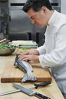 Male chef preparing salmon in kitchen