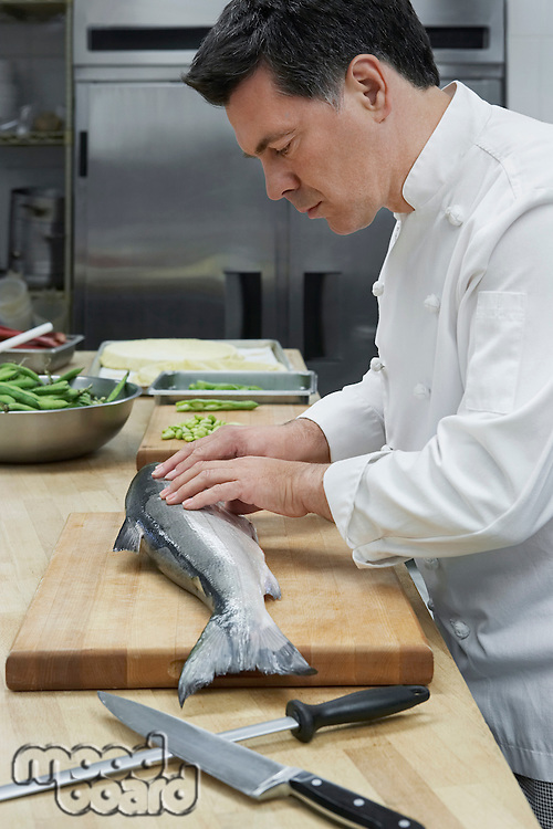 Male chef preparing salmon in kitchen