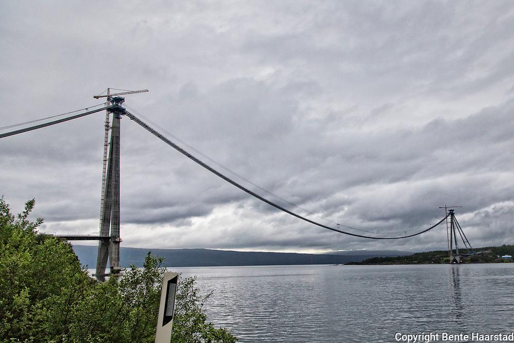 Bygging av H&aring;logalandsbrua utenfor Narvik i Nordland. Den skal krysse Rombaken mellom Karistranda, 2,2 kilometer nord&oslash;st for Narvik sentrum, og &Oslash;yjord, ti kilometer s&oslash;r for Bjerkvik. <br /> Brua blir en del av E6, og forkorter strekningen fra Narvik til Bjerkvik med 18 kilometer, og fra Narvik til Bj&oslash;rnfjell med 4-5 kilometer. Brua vil ogs&aring; avhjelpe vektbegrensinger p&aring; den eksisterende Rombaksbrua, og gi en mer rassikker forbindelse enn dagens E6. Dette har f&oslash;rt til at Narvik lufthavn, Framnes ble lagt ned 1. april 2017. Reisende blir henvist til Harstad/Narvik lufthavn, Evenes, i det kj&oslash;retiden til Evenes med bru, kortes ned fra ca. 60 til 40 minutter (fra 75 til 57 km). <br /> H&aring;logalandsbrua blir 1533 meter lang, med et fritt spenn p&aring; 1145 meter og blir med det Norges nest lengste hengebru etter Hardangerbrua. P&aring; grunn av stor forskjell i kostnad mellom de forskjellige alternativene til brukonstruksjon, bestemte Statens vegvesen v&aring;ren 2008 at bare hengebru skal vurderes i den videre prosjekteringen. Statens vegvesen (2008) kostnadsberegnet prosjektet til 1860 millioner kroner, inkludert tilknytningsveier og -tunneler.<br /> Bruprosjektet drives av H&aring;logalandsbrua AS, der Narvik kommune er majoritetseier med 75,95% av aksjene. Prosjektet er inne i Regjeringens forslag til Nasjonal transportplan for perioden 2010 til 2019, og det er foresl&aring;tt lagt til f&oslash;rste del av planperioden. I mai 2012 kunngjorde Samferdselsminister Magnhild Meltveit Kleppa at finansieringen for prosjektet er p&aring; plass.<br /> Byggestart var 18. februar 2013. I sammenheng med brobyggingen, ble rassikringstunnelen Tr&aelig;ldaltunnelen &aring;pnet den 11. september 2015. Brua vil etter planene &aring;pnes for trafikk sommeren 2018. Norsk bru blir kinesisk st&aring;lindustris inngangsbillett til Europa. <br /> Et kinesisk st&aring;lverk har vunnet konkurransen om &aring; levere det meste av 