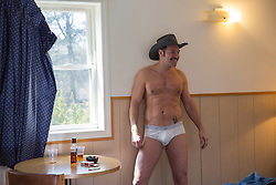 sexy cowboy in white briefs in a rundown motel room