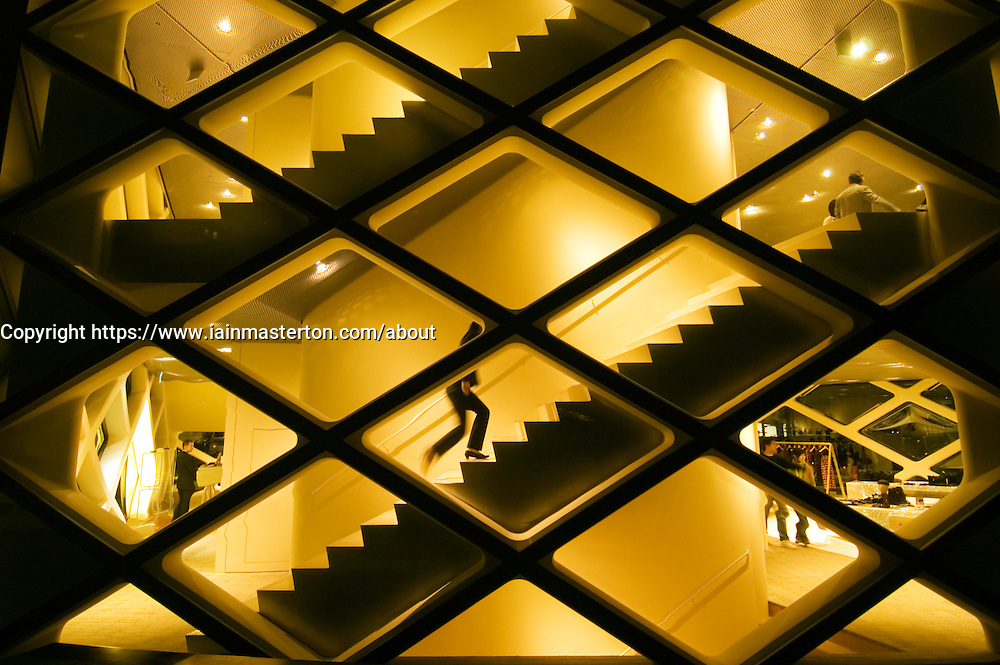 Exterior view of spectacular illuminated glass walled Prada store in Tokyo Japan