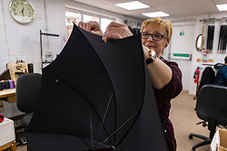 The umbrella's cover is fitted to its ribs. Craftspeople at Fox Umbrellas Ltd, a company in Croydon, Surrey, that has been going for over 150 years hand build quality umbrellas. Croydon, Surrey, March 06 2019.