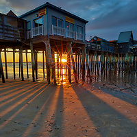 New England photography of a sunrise at Old Orchard Beach and its historic pier near Portland Maine. The sun was just crossed the horizon and created a beautiful sun star and rays. The long shadows of the wood pilings provided great leading lines into the frame. <br />