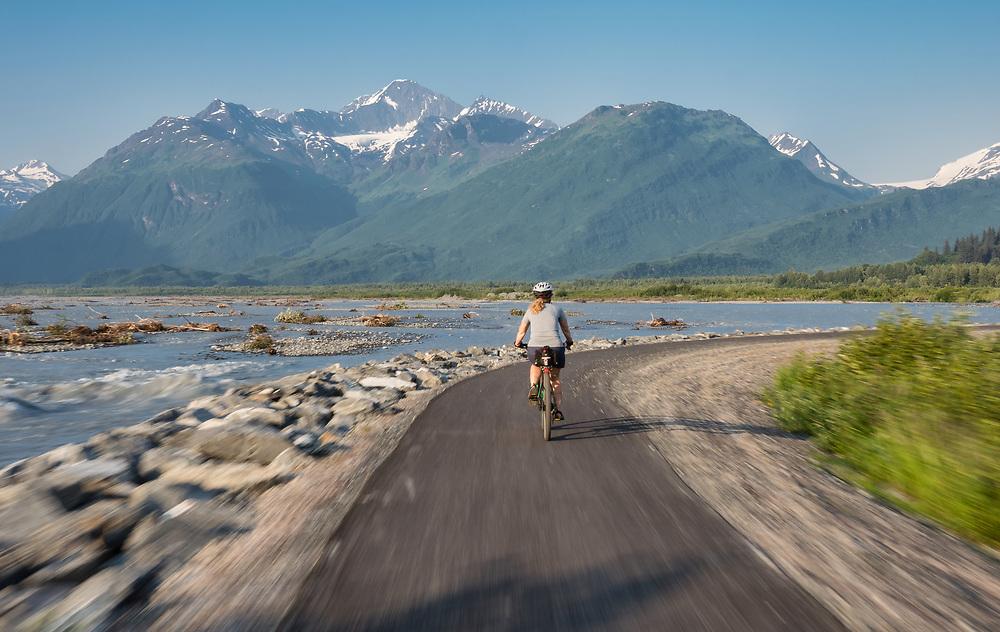 Cyclist biking on trail along the Valdez River in Southcentral Alaska. Summer. Evening. MR.